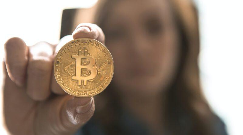 Een vrouw toont een bitcoin